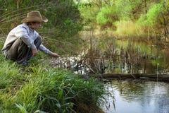 Счастливая рыбная ловля мальчика на реке Стоковые Изображения RF