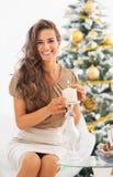 Счастливая свеча освещения молодой женщины около рождественской елки Стоковая Фотография RF