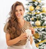 Счастливая свеча освещения молодой женщины около рождественской елки Стоковое Фото