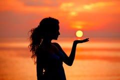 Счастливая свободная женщина наслаждаясь в заходе солнца моря Silhouetted против Стоковое Изображение RF
