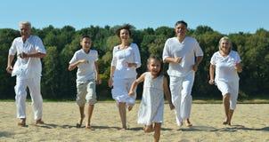 Счастливая семья бежать на пляже Стоковые Фотографии RF