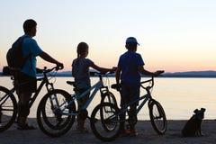 Счастливая семья - будьте отцом с 2 детьми на велосипедах с собакой Стоковое Изображение RF