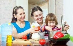 Счастливая семья варя вегетарианский обед Стоковое фото RF