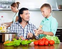 Счастливая семья варя еду Стоковое фото RF