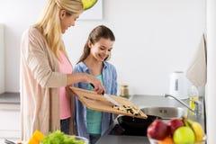 Счастливая семья варя кухню еды дома Стоковая Фотография