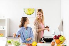 Счастливая семья варя кухню салата дома Стоковое фото RF