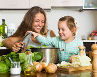 Счастливая семья варя суп Стоковые Фотографии RF