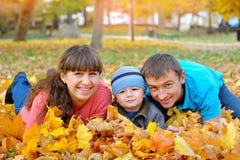 Счастливая семья в осени, листья желтого цвета Стоковое фото RF