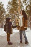 Счастливая семья в одежде зимы Мальчик держа руку его матери Стоковое Фото