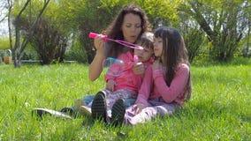 Счастливая семья в природе с пузырями мыла Женщина при девушки играя в свежем воздухе Малые девушки с мамой в парке видеоматериал