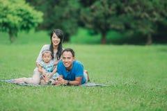 Счастливая семья лежа в траве стоковая фотография rf