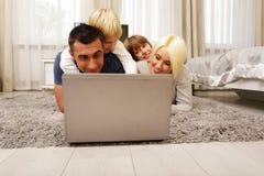 Счастливая семья лежа на ковре и играть Стоковые Изображения