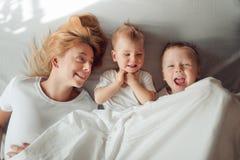 Счастливая семья лежа под белым одеялом в утре Стоковое Изображение