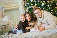 Счастливая семья лежа под рождественской елкой, усмехаясь Стоковые Изображения