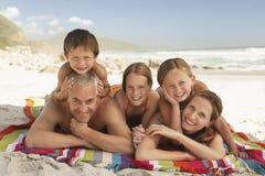 Счастливая семья лежа совместно на пляже стоковое изображение