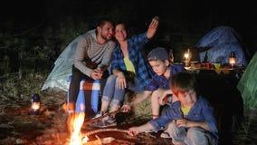 Счастливая семья делает фото на мобильном телефоне около лагерного костера в лесе, родителях с childs в лагерь перемещения делает сток-видео