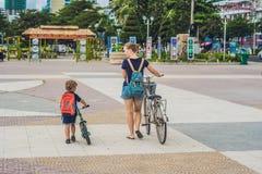 Счастливая семья едет велосипеды outdoors и усмехаться Мама на велосипеде Стоковое Фото