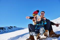 Счастливая семья едет розвальни в древесине зимы, жизнерадостных развлечениях зимы Стоковая Фотография