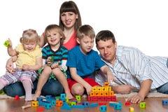 Счастливая семья играет на поле Стоковое Фото