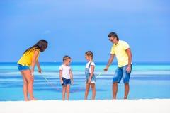 Счастливая семья играя на белом тропическом пляже Стоковые Изображения