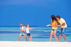 Счастливая семья играя на белом тропическом пляже Стоковые Фотографии RF
