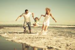 Счастливая семья играя на пляже на времени дня Стоковое Изображение RF