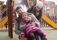 Счастливая семья играя на спортивной площадке Стоковая Фотография RF