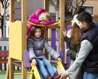 Счастливая семья играя на спортивной площадке Стоковая Фотография