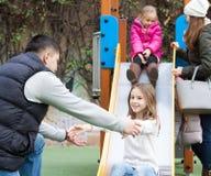Счастливая семья играя на спортивной площадке Стоковые Изображения