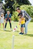 Счастливая семья играя сверчка совместно стоковое изображение rf