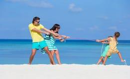 Счастливая семья играя совместно на белом пляже Стоковые Изображения