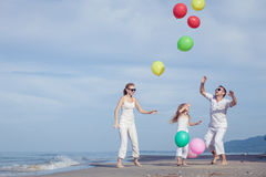 Счастливая семья играя с воздушными шарами на пляже на времени дня Стоковые Фотографии RF