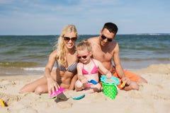 Счастливая семья играя с песком забавляется на пляже Стоковые Фотографии RF