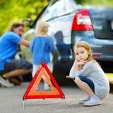 Счастливая семья изменяя колесо автомобиля стоковая фотография