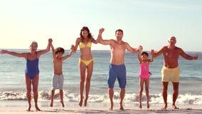Счастливая семья из нескольких поколений скача с руками вверх видеоматериал