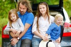 Счастливая семья из четырех человек идя к каникулам автомобиля стоковые изображения rf