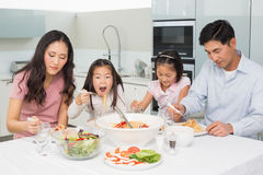 Счастливая семья из четырех человек наслаждаясь обедом спагетти в кухне Стоковые Фотографии RF