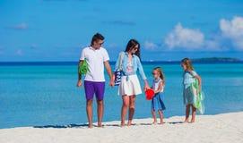 Счастливая семья из четырех человек на белом пляже Стоковые Фотографии RF