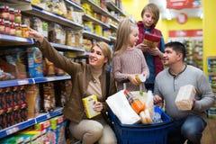 Счастливая семья из четырех человек покупая еду совместно стоковое фото rf