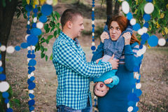 Счастливая семья имеет вечеринку по случаю дня рождения с голубыми украшениями в лесе Стоковое Фото