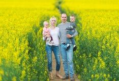 Счастливая семья имеет остатки на желтом поле рапса Стоковое Изображение RF