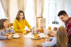 Счастливая семья имея завтрак в кухне их дома Стоковое Изображение RF