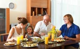 Счастливая семья имея здоровый обедающий с рыбами дома совместно стоковые изображения