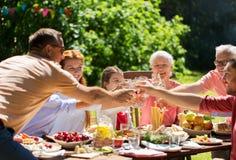 Счастливая семья имея обедающий или приём гостей в саду лета стоковое изображение rf