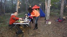 Счастливая семья имея пикник в лесе осени сток-видео