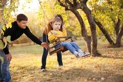 Счастливая семья имея потеху на езде качания на саде день осени Стоковая Фотография