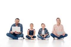 Счастливая семья используя smartphones, цифровую таблетку и компьтер-книжку Стоковые Изображения RF