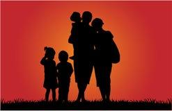 Счастливая семья и красивый заход солнца Стоковая Фотография RF