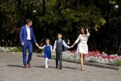 Счастливая семья идя вдоль пригородной улицы Стоковые Фото