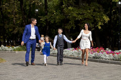 Счастливая семья идя вдоль пригородной улицы Стоковое Изображение RF